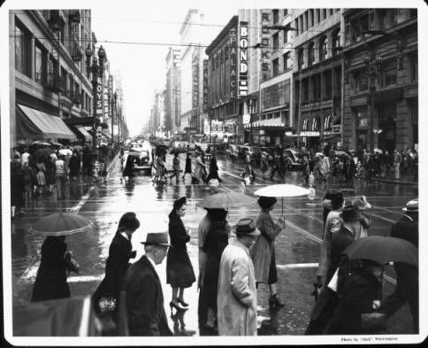 """Pedestrians crowd the crosswalks of Downtown on a rainy day :: """"Dick"""" Whittington Photography Collection, 1924-1987"""