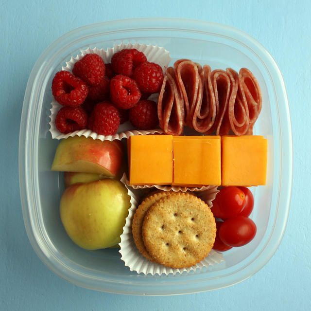 A simple bento to take on a plane: berries, salami, cheese, tomatoes, crackers and apples.