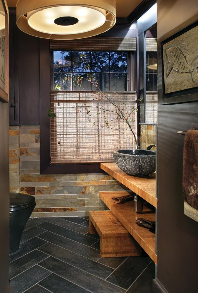 Such a lovely, earthy powder room. The textures of the granite sink, bamboo counters, slate wall tiles and wood-grain floor tiles create a lot of visual interest with a neutral color palette. Also, herringbone floors are delicious.