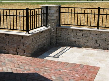 black fence ontop of stone wall | ... the height of the ...