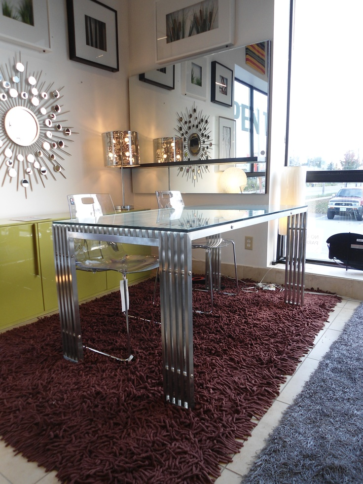 Contemporary stainless steel dining table with glass top