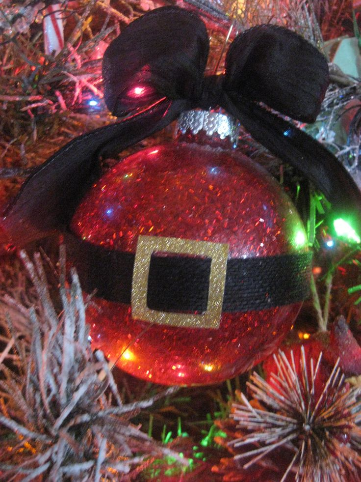 Santa ornament:  1. Sprayed adhesive inside the ornament. 2. Pour red glitter into the ornament. 3 Glue black ribbon around the ornament. 4 Make and glue a belt buckle made from gold glittered card stock onto the ribbon. 5. Add your favorite ribbon for hanging.