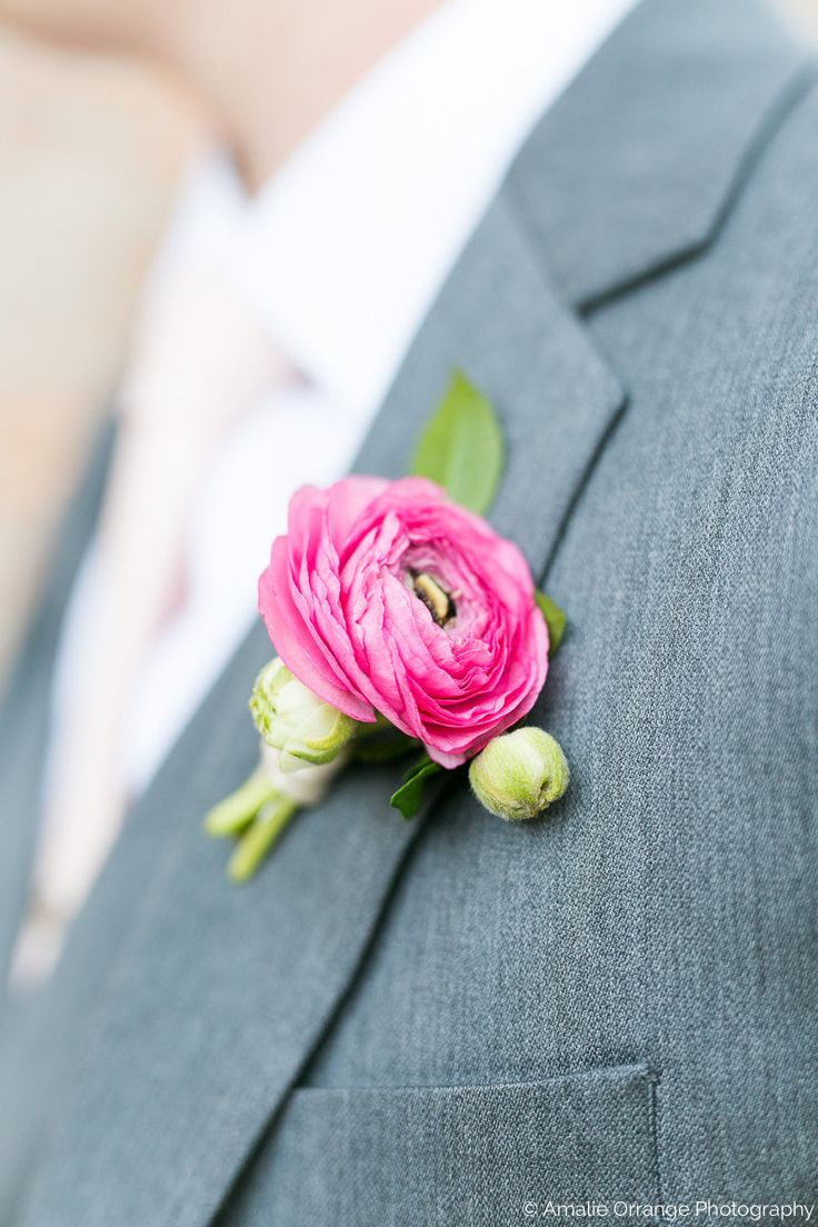 pink ranunculus bouttonniere on a grey suit.
