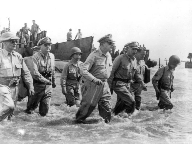 General Douglas MacArthur is accompanied by his officers and Sergio Osmena, President of the Philippines in exile, extreme left, as he wades ashore during landing operations at Leyte, Philippines, on October 20, 1944, after U.S. forces recaptured the beach of the Japanese-occupied island.