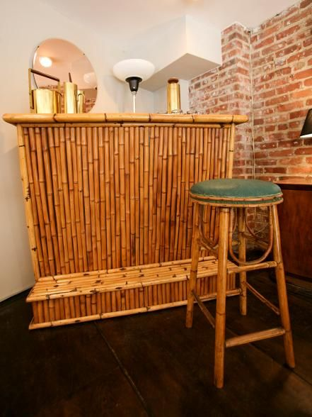 Tiki bamboo bar design with bar stool made of bamboo. This space has a rustic brick wall and dark wood flooring design. Detail shot of a bamboo bar area and bar stool used in homeowners Brandon Kinney and Dave Esposito's Home by Novogratz transformation.