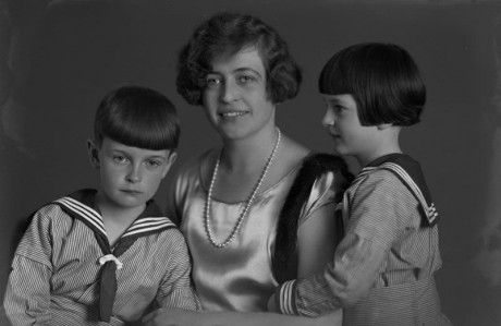 Porträtt av en kvinna klädd i klänning sittande i en stol med två barn i sjömansdräkt. Fotograferat i halvfigur. Foto taget av Ida Ekelund1925. Beställare: Fru kapten Kragh. KM 93676.17 i Kulturens samlingar.