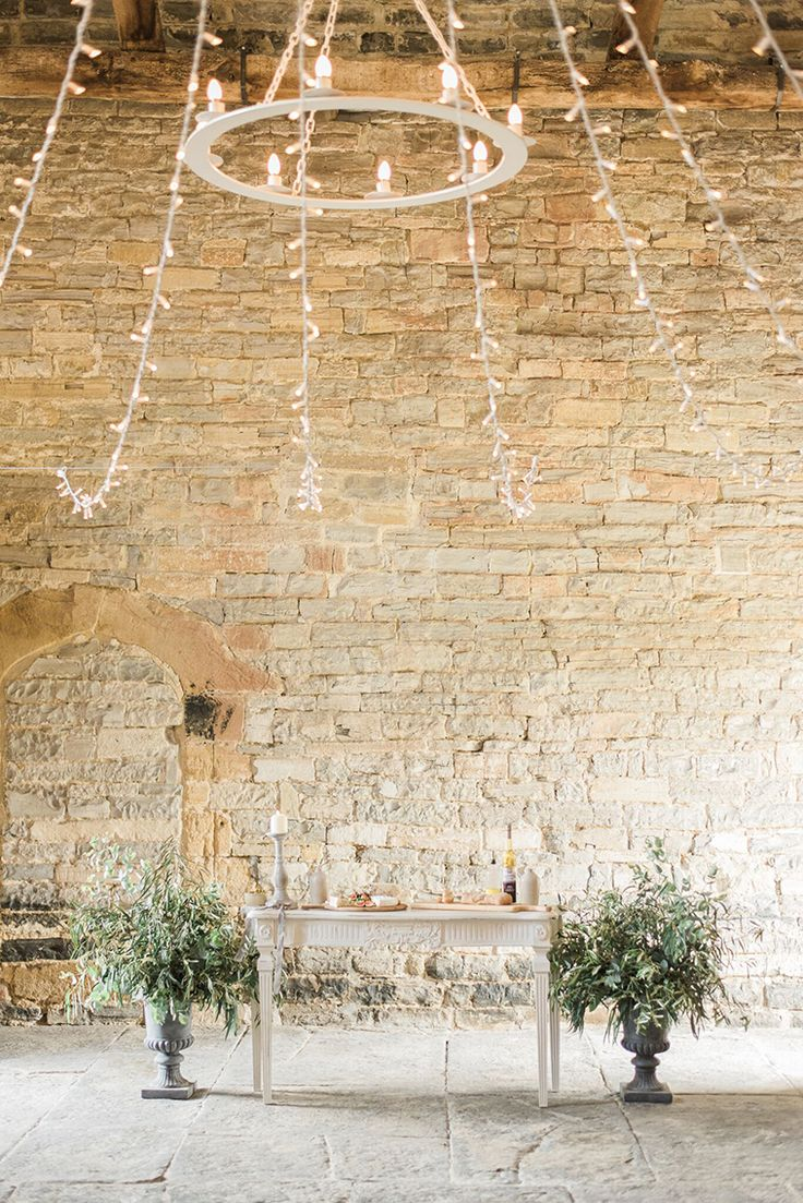Almonry Barn is a beautiful rustic stone barn wedding venue in the English Countryside - perfectly adorned with olive branch arrangements and a rustic cheese spread.  Photography by Victoria JK Lamburn | Dress and Accessories: Lady Evelyn | Flowers: The Rose Shed
