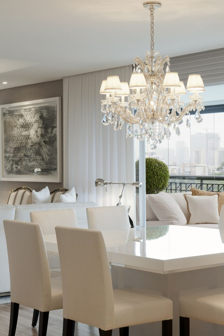 Glossy white dining table with a beautiful chandelier