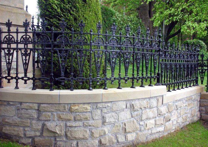 Кованый забор с каменным основанием подчеркнет стиль дома с прилегающим участком.