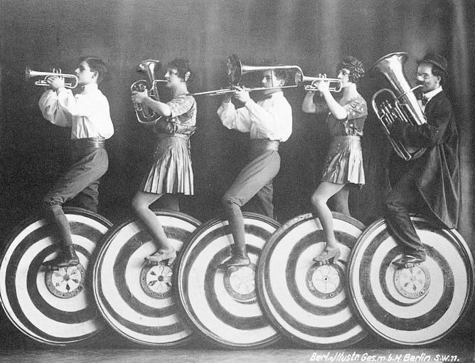 Circus band riding unicycles decorated like peppermint candies. Lordy, but that…