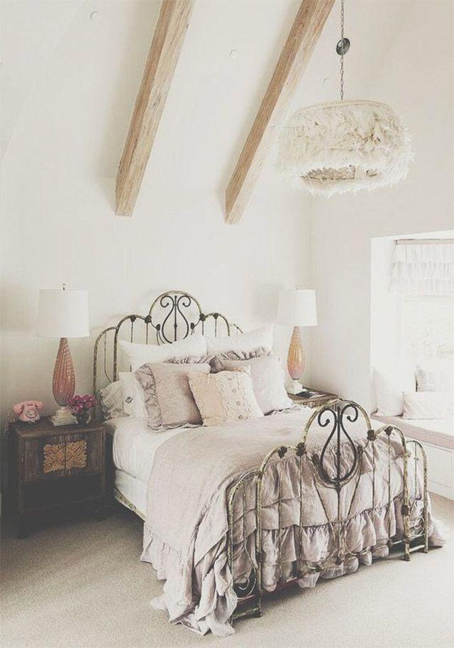 Cama y dosel metálico envejecido. Cubre colchón, sabánas, almohadones y cojines blancos. Cobertor y cojines lilas y rosa. Veladores a ambos costados de la cama con lámparas de mesa con base de pie rosa y pantallas blancas. Del techo cuelga una lámpara con pantalla blanca de flecos.
