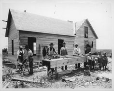 Carpenters building a home This photograph shows six carpenters building a wood-framed house and four barefoot children standing in a group by the work bench. Also visible are saws, lumber, nail box, window frame, wood plane, work bench, saw horses, and construction site rubbish. Date: Between 1910 and 1920