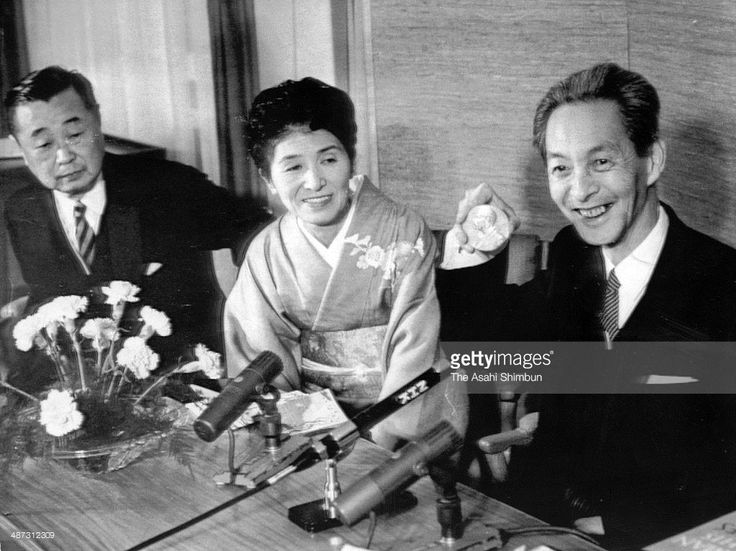 Japanese physicist Shinichiro Tomonaga (R) shows his Nobel Prize medal while his wife Ryoko (C) and Saitama University President Yoshio Fujioka (L) watch during a press conference at Swedish Embassy on December 10, 1965 in Tokyo, Japan. Tomonaga was unable to travel to Sweden as he had broken rib.