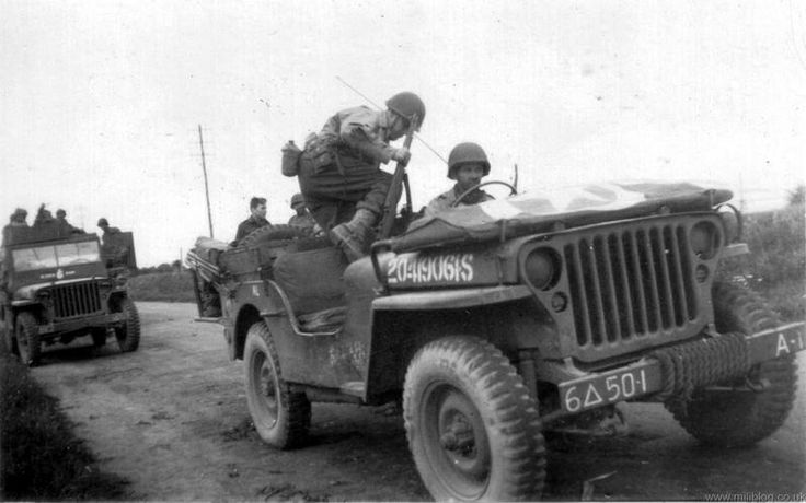 A GI with his M1 Garand loads up in the front Willys jeep. Date/location unknown.