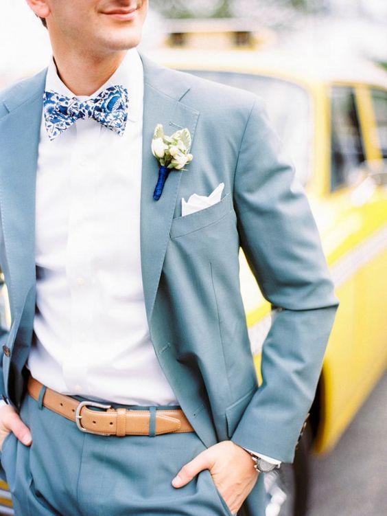 traje de color azul claro con una camisa blanca y una corbata de lazo fantasía con dibujos
