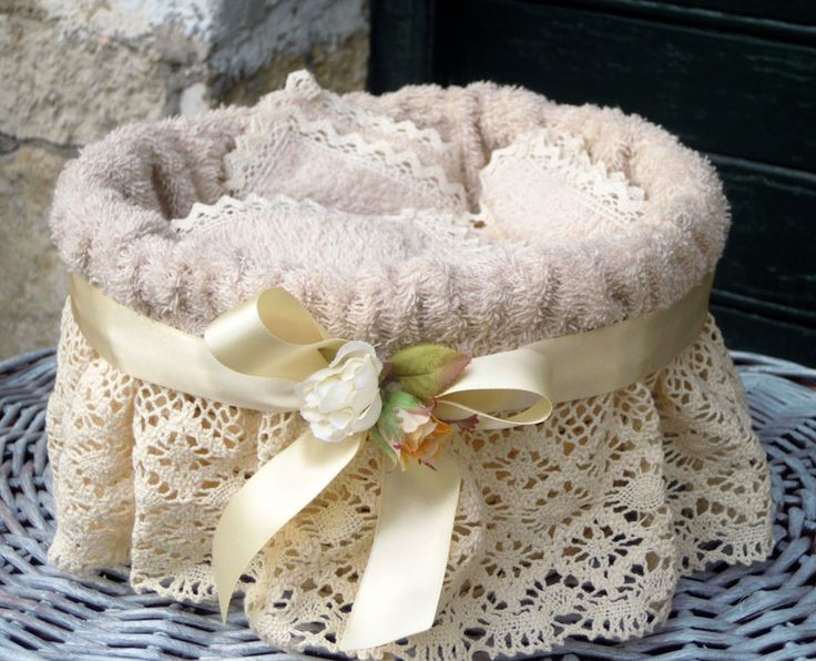 Wicker basket lined with terry washcloths ecru trimmed with ivory lace and satin bow with ivory roses.  Including: 3 washcloths size: 30x30 cm  Trash: h 15 cm, ⌀ 24 cm