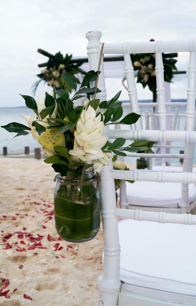 Cute mason jars filled with tropical flowers. #vanuatu #vanuatuweddings #destinationwedding #beachwedding #love #evrisamting #portvila #wedding #tropicalwedding #islandwedding