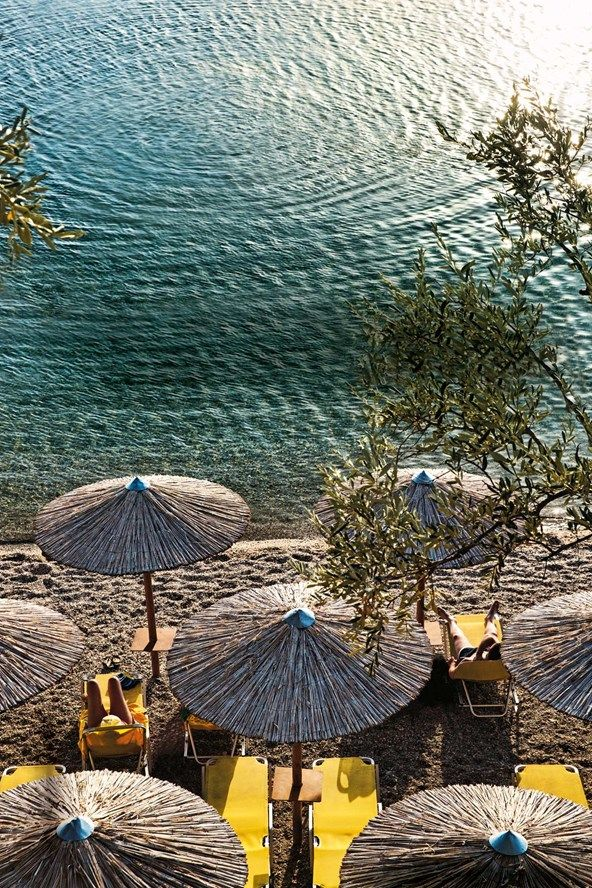 Bamboo parasols and yellow sunloungers on Afissos beach, Pelion, Greece | Greece travel ideas | Photo by Tom Parker for Condé Nast Traveller