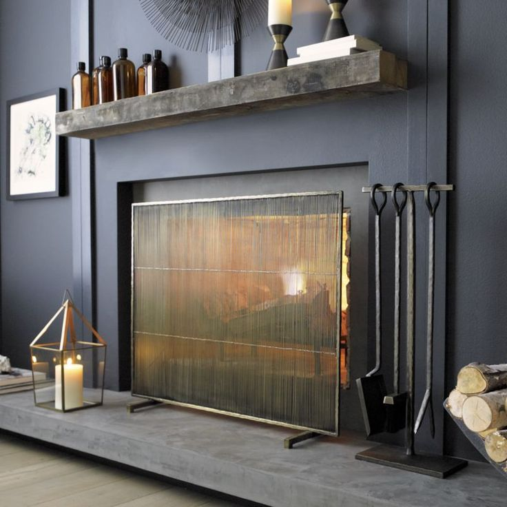 Mid-century modern styling screens the hearth in handcrafted iron with a warm, antiqued brass finish.  Freestanding, footed screen is rich with texture in both the wire construction and the patina. Iron with antiqued brass finishHandmadeClean with a damp clothMade in India.