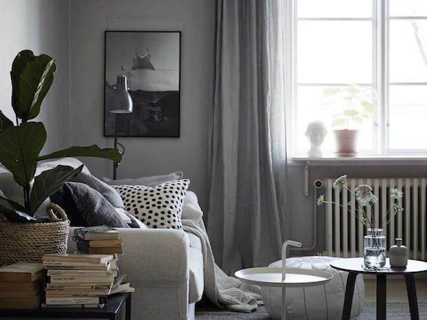 A sitting room in a calm, cocoon-like Swedish space in greys. Stadshem.: