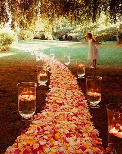 Create a romantic wedding aisle with rose petals in your favourite colour. The glass vases are filled with water and give it a classy touch. In the evening you can float candles on the water for a romantic night.