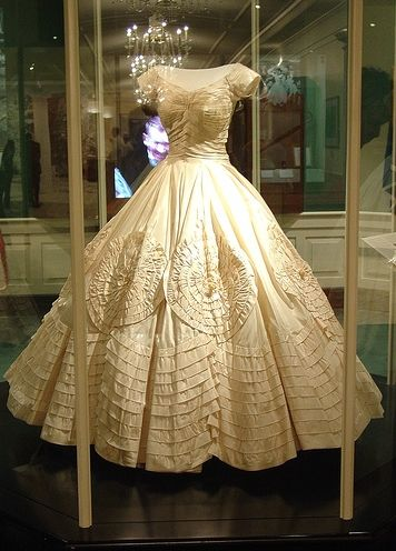 *JACQUELINE KENNEDY's ~ Original wedding dress: Centerpiece of the wedding dress is the skirt: at the bottom are applied bands of cloth interwoven + small flowers in wax.  Just above this, other bands are applied in fabric to form large concentric flowers.