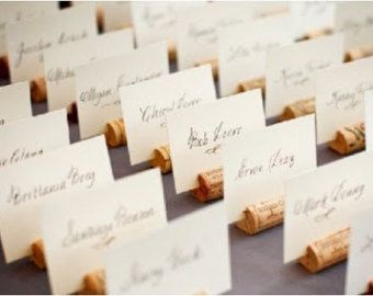 Recycled wine cork place card holders perfect for any wine or vineyard themed wedding, rehearsal dinner, or engagement party! These place card holders look beautiful displayed on your escort card and guest tables for your big day!  Each cork features a slit top and a flat bottom for ease of display. Please note that place cards are NOT included. Please choose a quantity in the drop down above for pricing.  Each cork is hand selected, cut, and the edges sanded smooth to create a polished and…