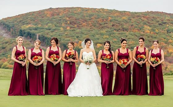 Romantic Red Autumn Wedding at Crystal Springs Resort in Northern New Jersey: Bridesmaids hold bouquets of red, orange, and yellow which echo the colors of the trees on the hillside behind them. The bridesmaid dresses are in a rich shade of cranberry red  | Photographer: POPography