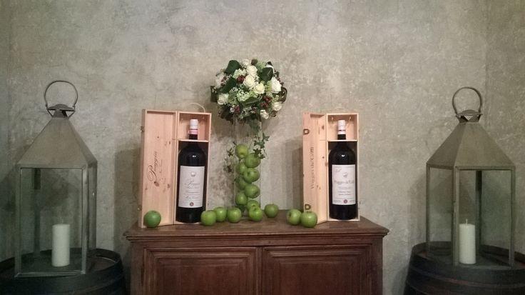 composizione con mele verdi in cilindro di vetro e sfera di fiori misti