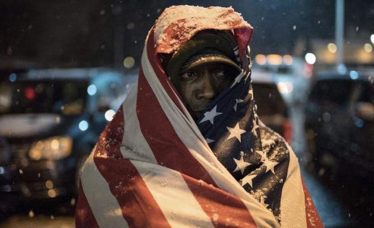 Un manifestante de Ferguson (Saint Louis, Misuri), se cubre con la bandera de EE UU. / Alexey Furman (EFE)
