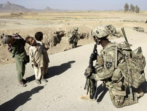 Afghan children joke with an American soldier during a patrol in a village in Arghandab Valley.