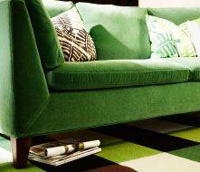 Soggiorno con divano a tre posti e cuscini in velluto verde.