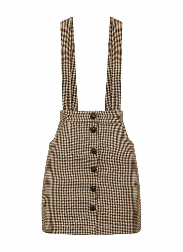 The Bettina Dogtooth Brace Skirt with pockets and detachable brace straps can be worn as a classic mini or be transformed into a pinafore-style piece.