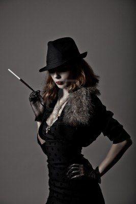 Retro colpo di donna gangster in cappello fedora e abito da sera, portavoce di partecipazione photo