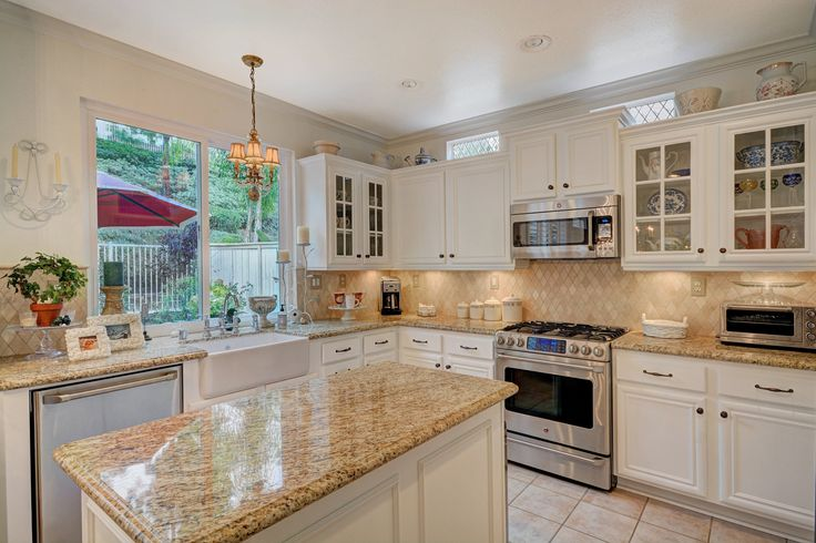 A kitchen made up of pink purple walls, white blade curtains, a small squared granite countertop island table, with traditional lighting fixtures, stainless steel oven, and stainless steel refrigerator, with white cabinets make up this kitchen. - All from a different angle.