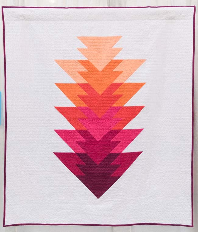 Arrowhead Quilt - Berry Colorway by Kristi Schroeder, 2015 | The Modern Quilt Guild....The design of the arrowhead quilt was inspired by my time spent in the mountains of New Mexico as a child while hiking throughout the Pecos wilderness and discovering fossils along the way.
