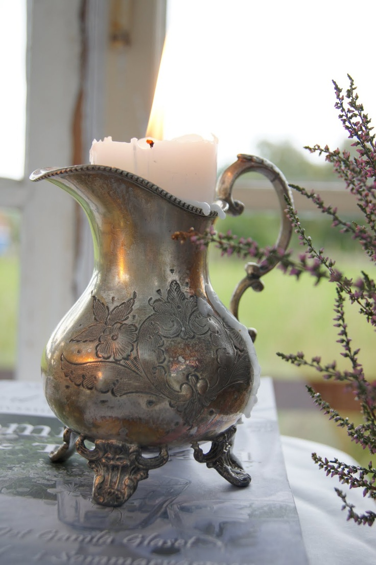 candle in silver pitcher