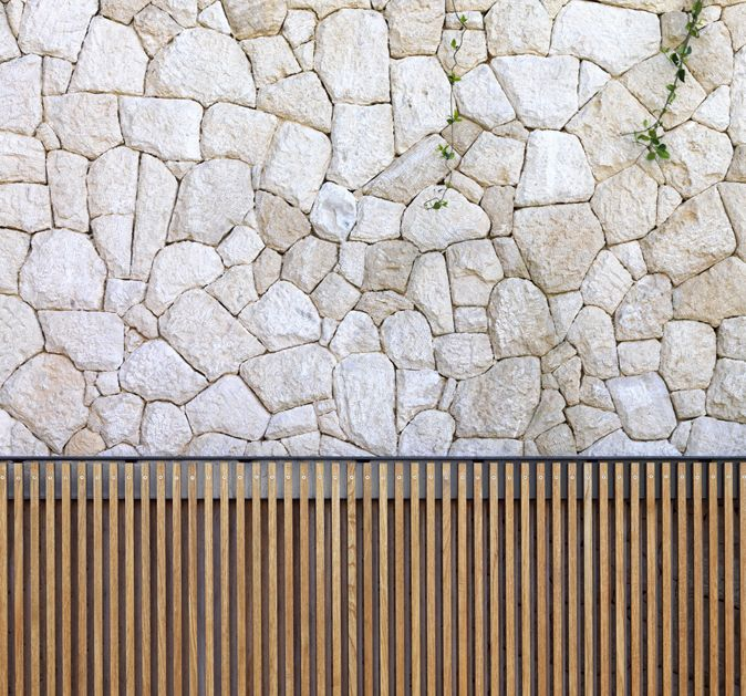 Courtyard cobble stone wall; honed teak rods on exterior. architect: tobias partners