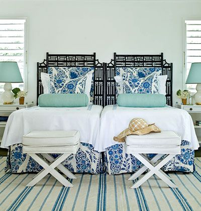 Symmetrically Styled    Outfitted with twin beds, lamps, side tables, and folding benches, this guest bedroom uses traditional blues and whites to create a soothing coastal space. Chocolate brown cane-and-rattan headboards add a graphic, tropical touch.