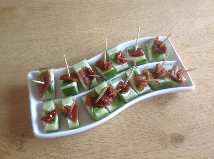 Komkommer- halveren en uithollen- roomkaas of roomkaas met kruiden in holte - in koelkast laten opstijven- basilicumblaadje+ stukje zongedroogde tomaat.  Ziet er feestelijk uit, simpel en heerlijk!  AK