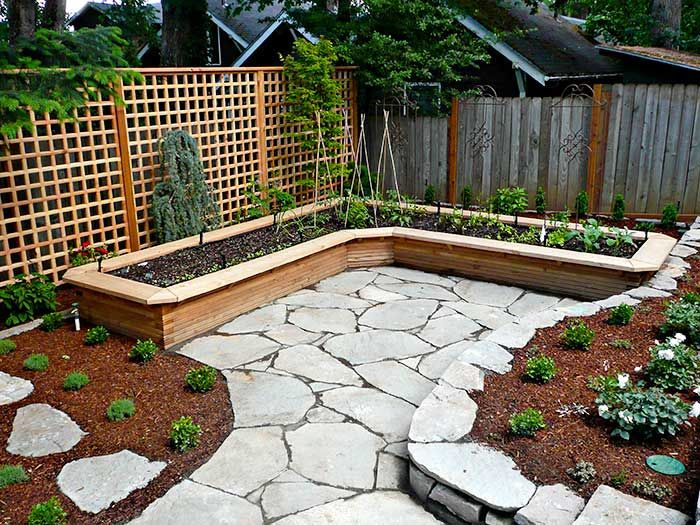 An L-shaped vegetable raised bed hugs the northeast corner of the lower backyard, with a tall trellis forming the backdrop and giving privacy, late May