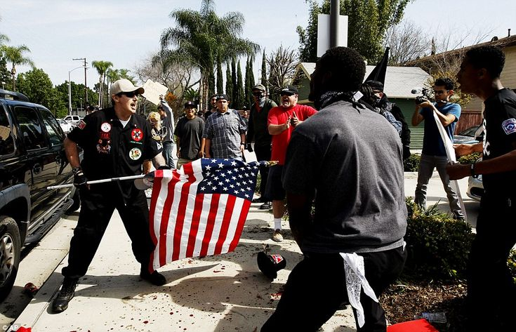 A Klansman, left, uses an American flag to fend off angry counter protesters near a planne...