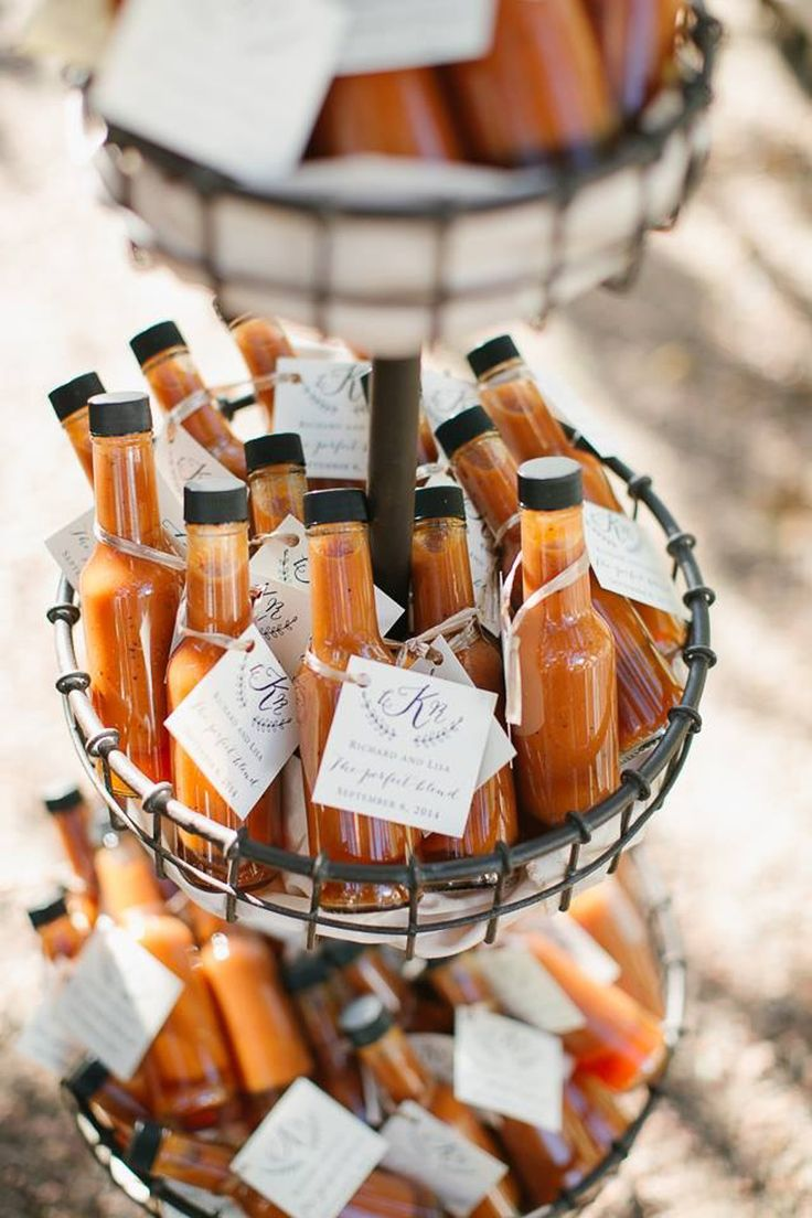 Miniature bottles of hot sauce gathered in a basket and used as wedding favors. Love the creative tag design! #weddingdetails #weddingfavors #hotsauce