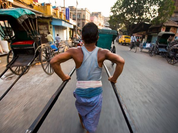 <p>Photo: A man pulling a rickshaw through a street</p>
