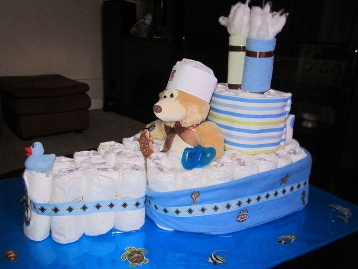 Super steam boat with over 45 diapers, 2 receiving blankets, 2 wash cloths with smoke coming out, decorated on a board to simulate water and fishes swiming around. A teady bear with sailor hat, a small duck in front and a pacifier .Inspired by other boats saw on pinterest.