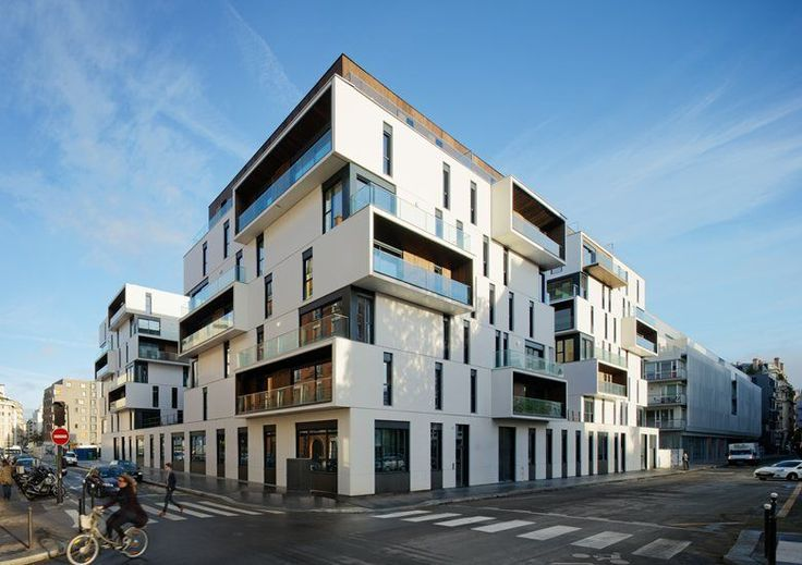Apartment complex by Ameller Dubois & Associés, Paris, France. Polished white concrete façade, implemented by large prefabricated elements ; loggias and attics dressed entirely of wood.
