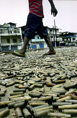 2004 - Carolyn Cole, Los Angeles Times. WAR UNDERFOOT: Bullet casings carpet a street in Monrovia, at the heart of the battlefield between government and rebel soldiers. Businesses closed for weeks as the battle raged.