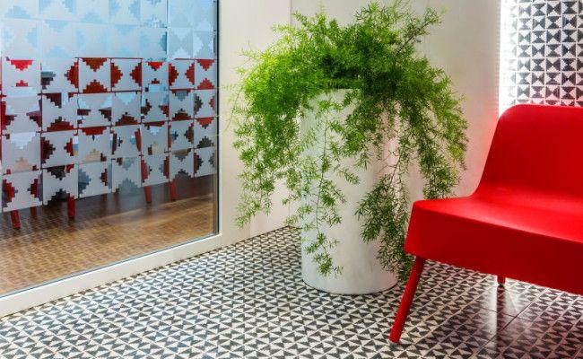 Oficinas, zona de espera y sala de juntas al fondo. Mobiliario en polietileno. Revestimiento imitación mosaico hidráulico, diseño geométrico. Vinilos en cristales con mismo diseño.
