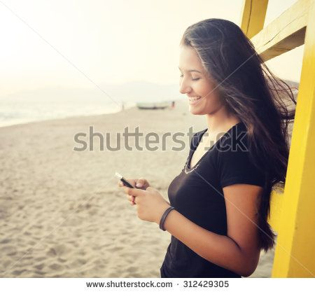 Beautiful young teenager while using the smartphone on the beach