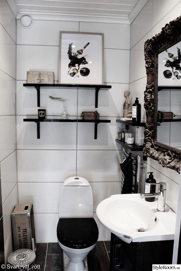 svarta hyllor,toalett,vitt kakel,gammaldags spegel,artprint,konsttryck,tavla,toalettstol,tvättställ,wc,tvättfat,handdukstork,glödlampa vas